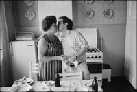 Jerzy Kichler, with bag of leftover food, saying goodbye to his mom in her Krakow kitchen. 1983