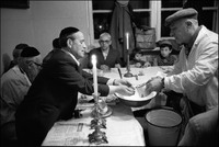 The ceremonial washing of hands. Natan Cywiak, shamus, at Passover Seder held in Warsaw's kosher kitchen. Holding cup and basin is Solomon Klingkoffer. 1979