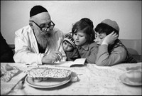 Moshe Shapiro teaching children prayers from the Hagaddah after Passover Seder in Warsaw's kosher kitchen. 1979