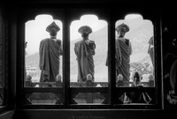 Buddhist monk musicians greet the monk king from Temple rooftop while he makes his way to his winter palace. Boy monk in foreground. Kingdom of Bhutan. 2004